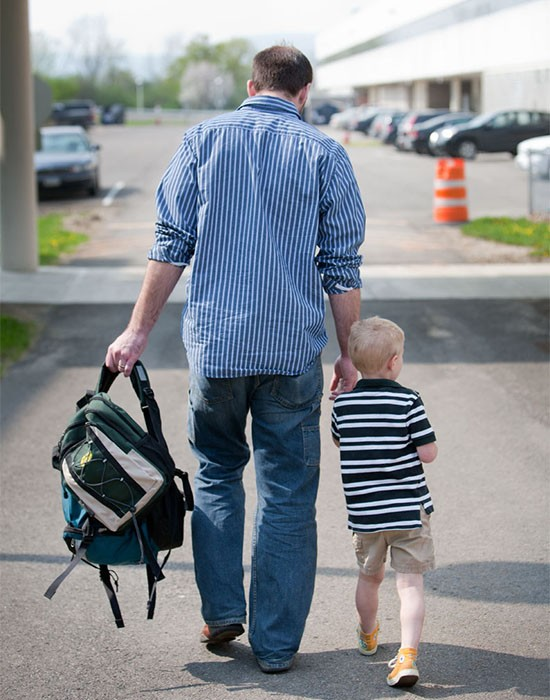 Parent and child walking with backpack