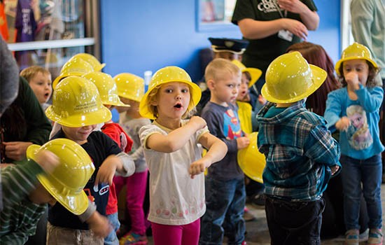 Kids from child care center wearing toy hard hats