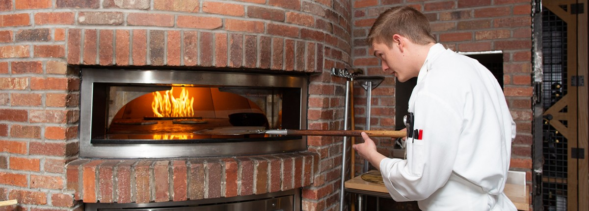 Culinary Student putting pizza in brick oven at Coltivare