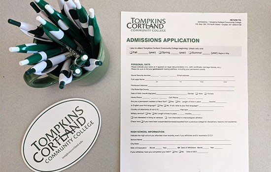 Tompkins Cortland application, pens, and sticker