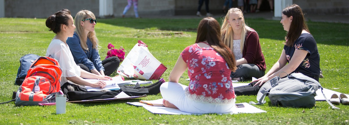 Students sitting in circle on Dryden Campus lawn