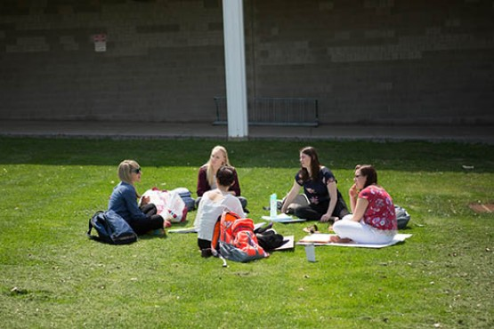 Group of students sitting in circle on campus lawn
