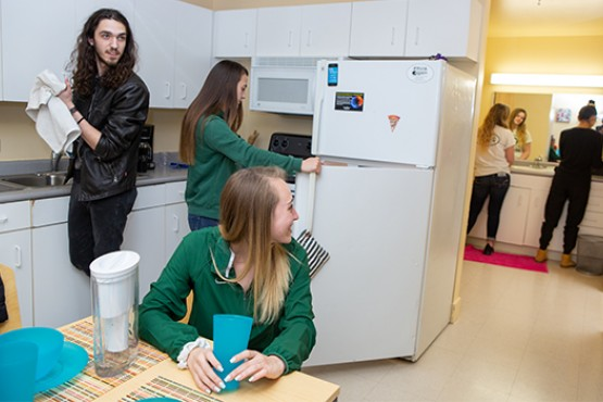 Students mingling in campus dorm kitchen