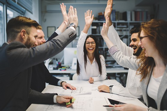 Business professionals high-fiving in meeting